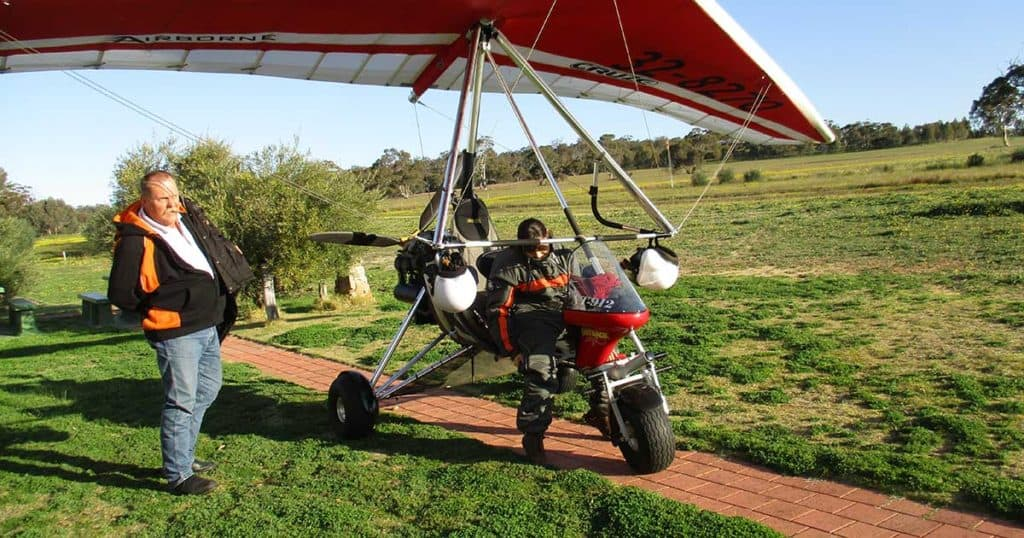 Amellia Formby and Gordon Marshall next to a red microlight aircraft at White Gum Farm