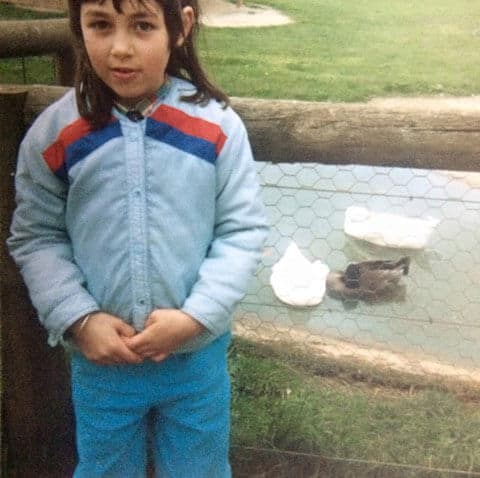 Amellia Formby at seven years old standing next to a fence in front of a pond with three ducks in it