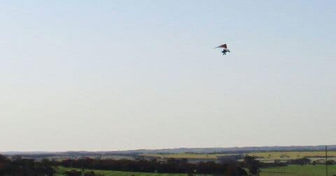 A microlight flying over White Gum Farm