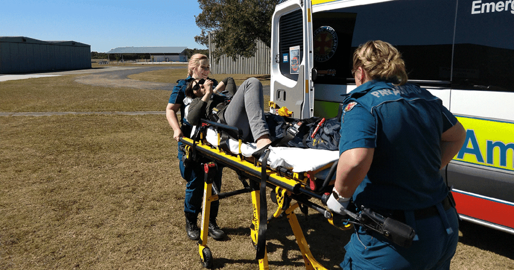 Amellia Formby on a stretcher being wheeled to an ambulance by two paramedics