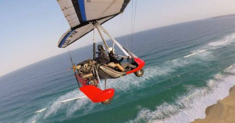 A microlight flying over the beach