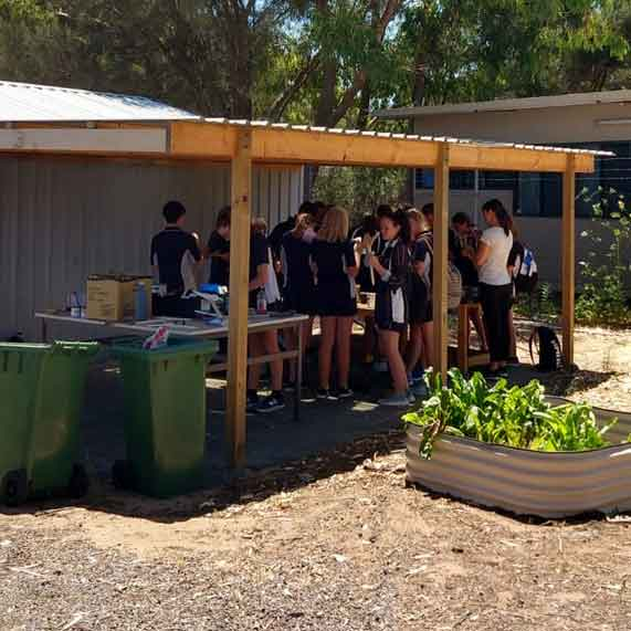 Students standing under a shelter painting shorebirds for the Flock Oz