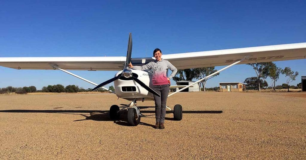 Amellia Formby standing next to the propeller of a white Foxbat ultralight aircraft