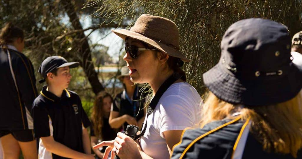 Amellia Formby wearing hat and binoculars out in the field with students
