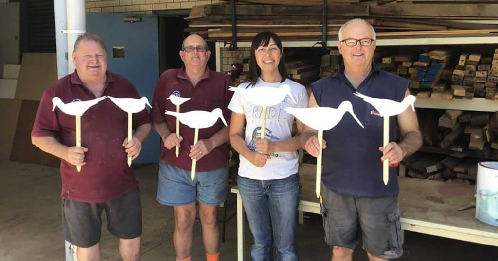 Amellia Formby with volunteers from The Mandurah Men's Shed holding shorebird cutouts