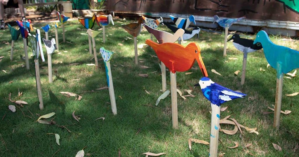 Painted cutouts of shorebirds for the Flock Oz on stakes in the grass