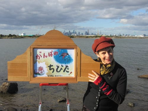 Author, Jackie Kerin, standing next to a kimibashi storybox in front of a river in Melbourne
