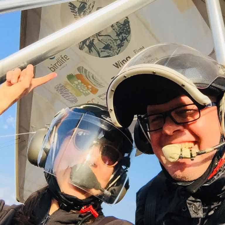 Selfie of Amellia Formby and Steve Klose wearing microlight helmets