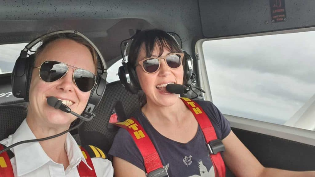 Selfie of Amellia Formby and her flight instructor, Georgia, wearing headsets and sunglasses in the cockpit