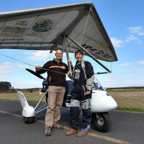Amellia Formby and Ken Jellef standing next to white microlight
