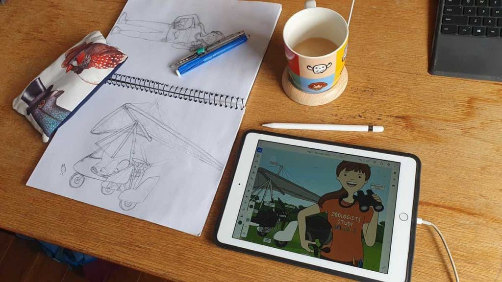 Desk with a sketchbook, iPad and a cup of tea on it.